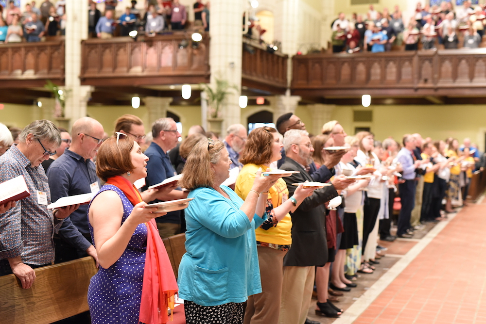 worshipers fill the sanctuary, raising hands and singing